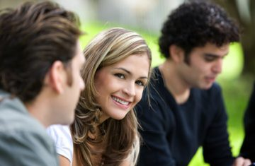 group of friends outdoors in a park smiling - focus on woman